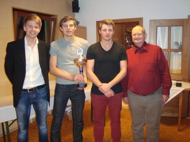 Der 1. Vorstand Georg Schmöller (r.) überreichte zusammen mit dem 2. Vorstand Stephan Katzbichler (l.) den Gewinnern des Weihnachts-Doppelturniers Tobias Maierhofer und Philipp Bauer (Mitte) den Wanderpokal.