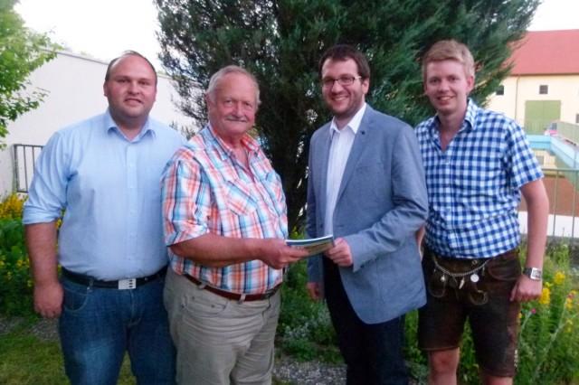 Im Beisein von Förderkreisvorstand Florian Geier (l.) und 2. Vorstand Stephan Katzbichler (r.) überreichte Vorstand Georg Schmöller das 1. Exemplar der Festschaft Bürgermeister Florian Gams.